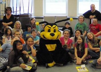 FSB's Buzzy Bee sitting with local students
