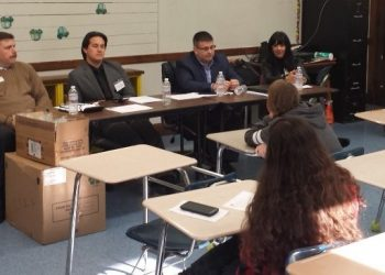 A panel of bankers teach students in school about financial education