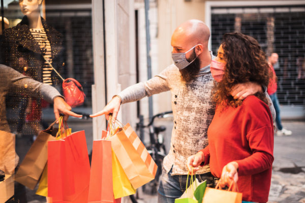 Beautiful young couple shopping together with face mask